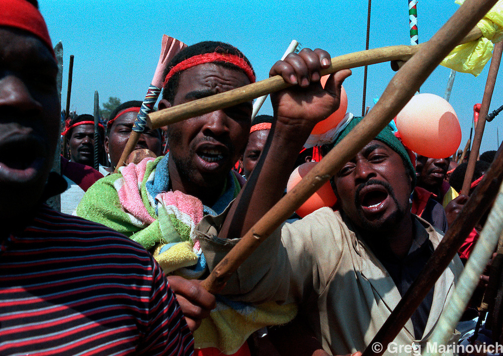 POLITICS TOKOZA SOUTH AFRICA 1990: Inkatha Freedom Party members formed in a traditional regiment march on African National Congress allied residents and fighters in Tokoza, South Africa, 1990. Part of The Dead Zone series. (Photo by Greg Marinovich / Getty Images)