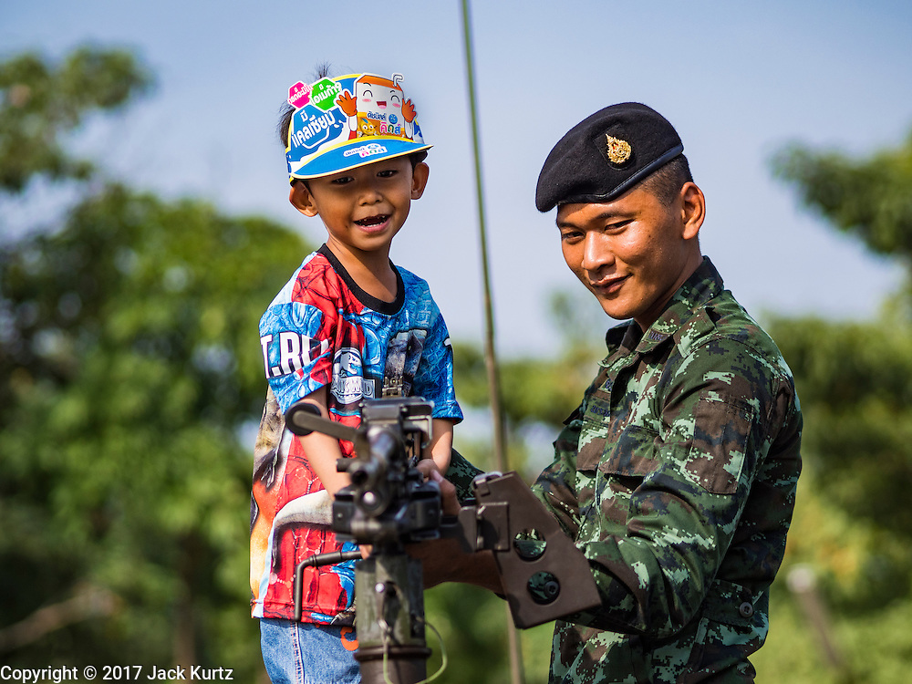 """14 JANUARY 2017 - BANGKOK, THAILAND: A Thai soldier helps a child look at a FN MAG machine gun mounted on a HUMVEE during Children's Day activities at the King's Guard, 2nd Cavalry Division base in Bangkok. Thailand National Children's Day is celebrated on the second Saturday in January. Known as """"Wan Dek"""" in Thailand, Children's Day is celebrated to give children the opportunity to have fun and to create awareness about their significant role towards the development of the country. Many government offices open to tours and military bases hold special children's day events. It was established as a holiday in 1955.     PHOTO BY JACK KURTZ"""