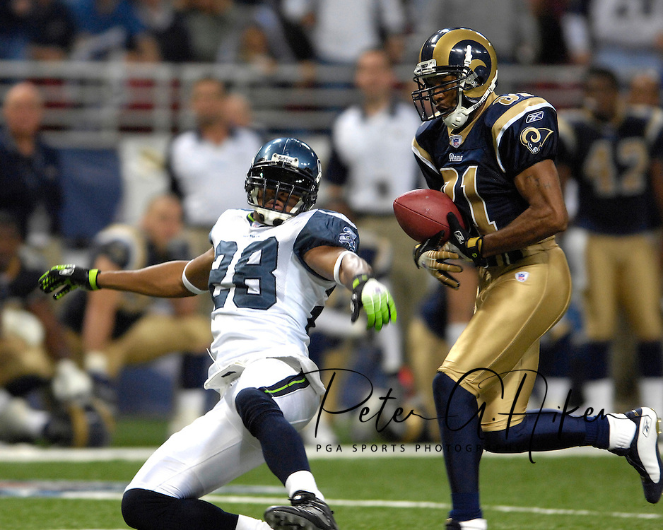 St. Louis Rams wide receiver Torry Holt (81) juggles a touchdown catch late in the fourth quarter as Seattle safety Michael Boulware (28) falls to the ground, giving the Rams a 28-27 lead at the Edward Jones Dome in St. Louis, Missouri, October 15, 2006.  The Seahawks beat the Rams 30-27.<br />