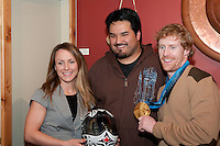 Jon Montgomery shares his gold medal win in the mens' skeleton with Tsimshian artist Philip Gray and his girlfriend at the Black Tusk Gallery in Whistler during the 2010 Olympic Winter Games. Montgomery commissioned Gray to paint his animal totem, the Thunderbird, on his helmet. In local first nations culture the Black Tusk is considered the nest of the Thunderbird, and so was Montgomery's choice in locating an artist to create his helmet design.
