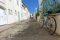A blue bicycle leans against a green iron fence in a shade-dappled Mediterranean street in Saintes-Maries-de-la-Mer, France. White buildings on the street reflect the sun, beneath a solid blue sky.