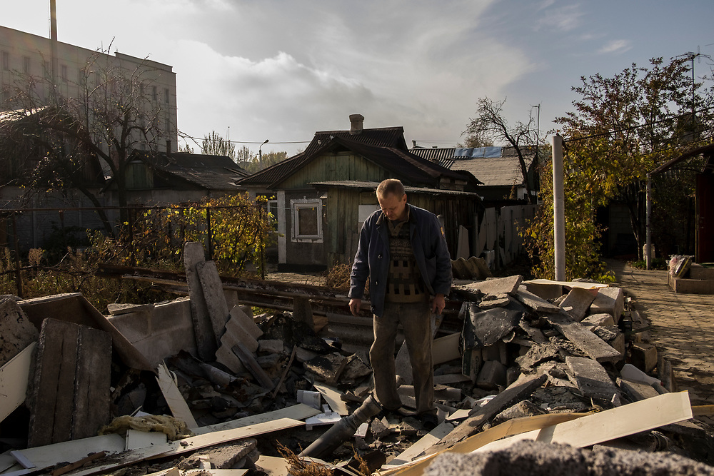 A local man examines an unexploded missile lodged among the rubble of his garden shed, close to Donetsk Airport.
