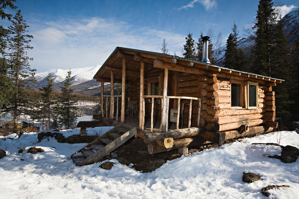 The remains of snow from a late winter storm surround the public use cabin at Eagle River Nature Center, Eagle River in Chugach State Park, Alaska as morning light highlights the snow-capped  Chugach Mountains in the background.