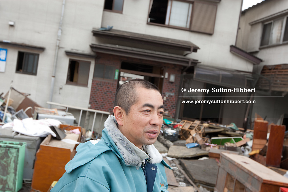 Minoru Shimokawara outside the destroyed house (in rear of picture) of his late grandfather - the 104 year old Takashi Shimokawara, who lost his life in the March 11th tsunami in Kamaishi city, Tohoku region, Japan, on Tuesday 12th April 2011. Takashi Shimokawara lost his life in the tsunami, along with his son and daughter-in-law. Takashi Shimokawara was known for the world records he held in javelin throwing in the over 100 year olds category of the sport.