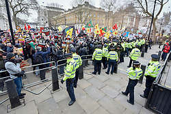 "© Licensed to London News Pictures. 17/03/2018. LONDON, UK. Police manage crowds after a flare is thrown into Downing Street during a ""March against Racism"", where people walked from Portland Place to Downing Street, calling for a united movement for everyone against all forms of racism.  Photo credit: Stephen Chung/LNP"