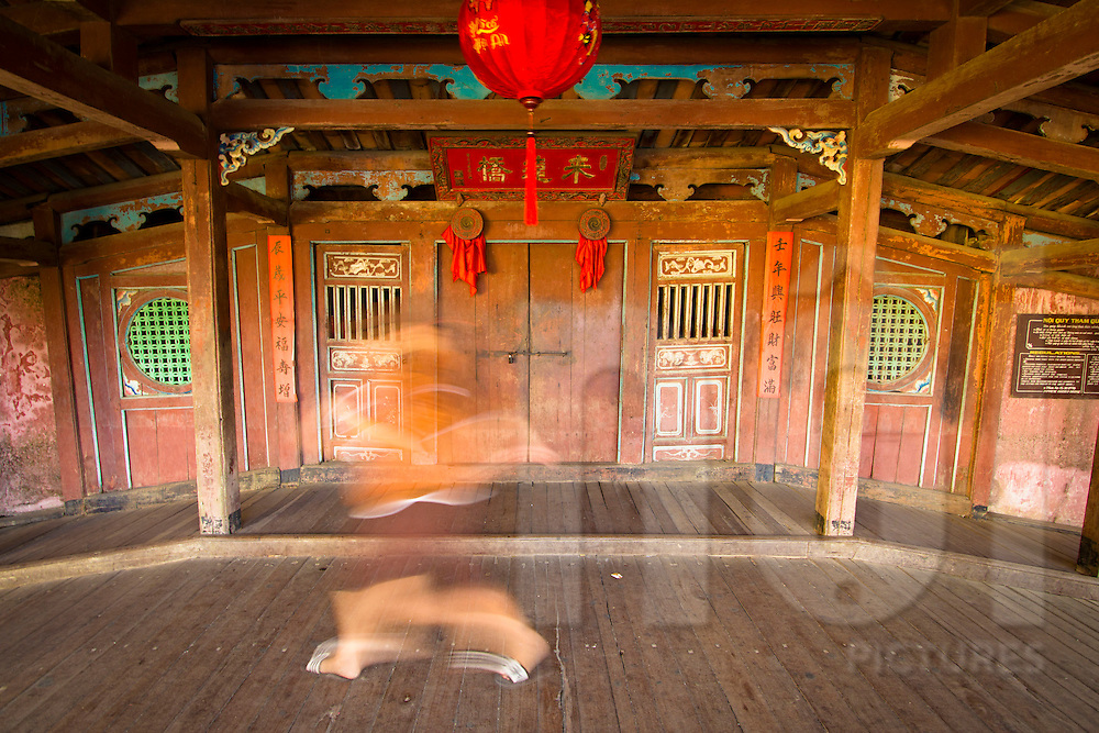 Blurred ghost-like figure crosses the Japanese bridge in Hoi An. Built in 17th century Vietnam by a Japanese craftsmen, it is also known as the Bridge pagoda (Chua Cau). Central Vietnam, Southeast Asia, 2012.
