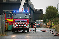 © Licensed to London News Pictures. 07/10/2016. Leeds UK. 100 fire fighters & 20 engines have been fighting a huge fire at the Allied glass factory in Leeds. The fire broke out just after midnight on the Towngate link in Cross Green. Photo credit: Andrew McCaren/LNP