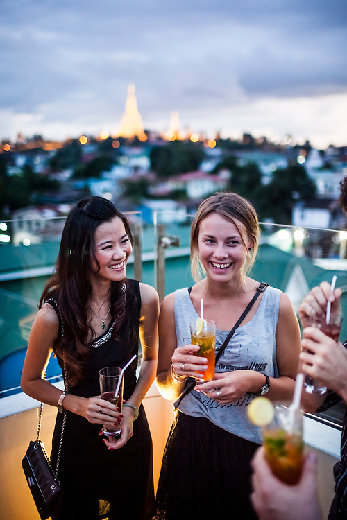Travelers on a rooftop bar with a view of Shwedagon Pagoda in Yangon.