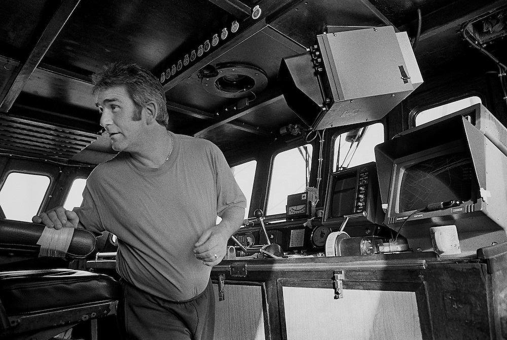 PZ 198, the 'Aaltje Adriaantje'.<br /> Charlie, skipper, in the wheelhouse.<br /> <br /> These boats are out for seven days at a time in all weathers and the nets are hauled up every three hours around the clock. The crew consists of five self-employed fishermen who share the profits of the catch.