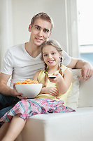 Portrait of father and daughter watching TV with bowl full of wheel shape snack pellets