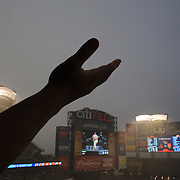 A fan checks the rain drops during a rain delay before the New York Mets V Arizona Diamondbacks Major League Baseball game  at Citi Field, Queens, New York. USA. 3rd July 2013. Photo Tim Clayton