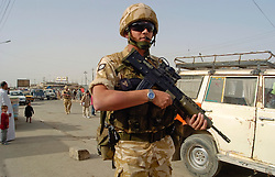 Soldier from the East and West Riding Regiment, Territorial Army, wearing desert camouflage, Kevlar helmets and body armor, carrying SA80 assault rifles which are fitted with SUSAT sights on foot patrol through the streets of Basra during Op Telic in March 2005