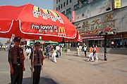 Wangfujing Dajie shopping street and pedestrian zone. Policemen under a McDonald's umbrella.