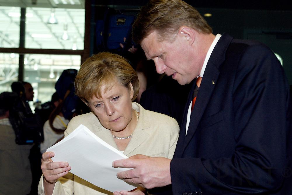 BRUSSELS - BELGIUM - 16 JUNE 2006 -- EU SUMMIT --  Angela MERKEL, German Federal Chancellor, studies a paper with Matti VANHANEN (R), Finnish Prime Minister, and the Minister for Foreign Affairs Erkki TUOMIOJA (L).  PHOTO: ERIK LUNTANG /