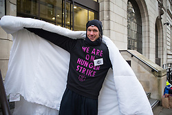 London, UK. 19 November, 2019. A hunger striking climate activist from Extinction Rebellion stands outside the Liberal Democrat headquarters on the second day of an 'Election Rebellion' hunger strike with three demands for election candidates: to tell the truth by declaring a Climate and Ecological Emergency, to promote policies to halt biodiversity loss and reduce greenhouse gas emissions to net zero by 2025 and to help the Government create and be led by a Citizen's Assembly on climate and ecological justice.