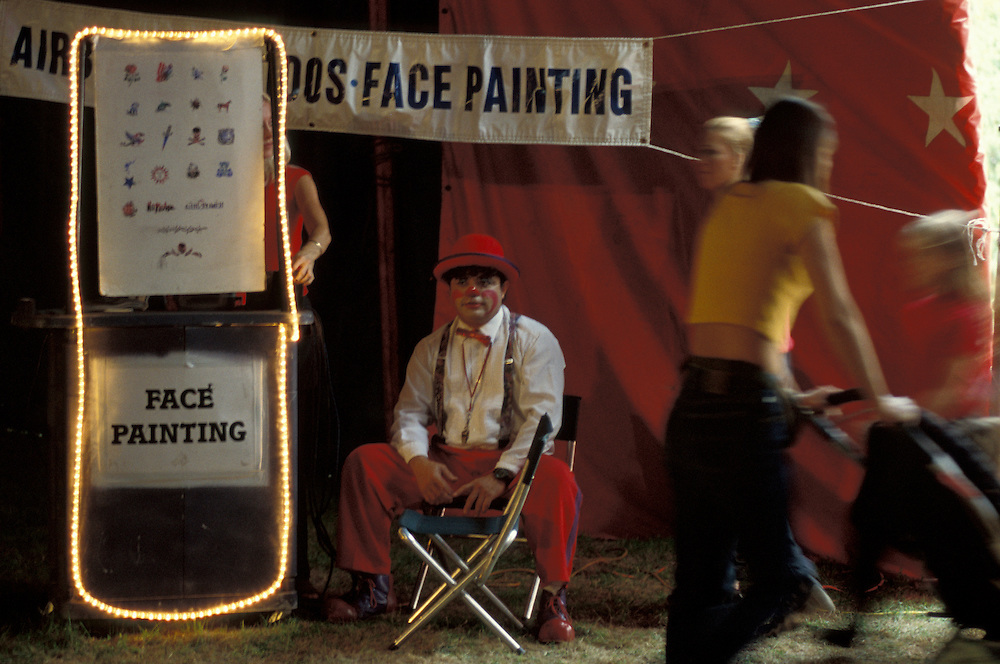 """Clown offers face painting to circus visitors.  Bentley Bros. circus, one of the few remaining """"mud show"""" circus performing under a canvas big top."""