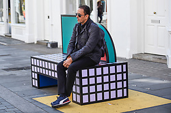 "© Licensed to London News Pictures. 14/09/2019. LONDON, UK.  A tourist sits on a sculptural bench as ""Walala Lounge"" opens in Mayfair's South Molton Street.  Artist and designer Camille Walala's installation comprises 10 sculptural benches, accompanied by planters and a series of oversized flags strung, bunting-style, from shopfront to shopfront, converting the street into an immersive corridor of colour as part of this year's London Design Festival.  Photo credit: Stephen Chung/LNP"