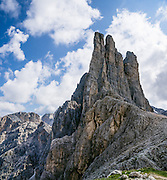 Hike a steep path to see the Vajolet Towers/Torri del Vaiolet (2813 m) in the Rosengarten/Catinaccio Dolomites, Italy, Europe. From Pera di Fassa village (in Pozza di Fassa comune in Val di Fassa), in Trentino-Alto Adige/Südtirol region, Italy, take a bus or lift to visit Rifugio Gardeccia Hutte or other lodging and hike upwards in the Rosengarten mountain massif. 200 million years ago, Triassic coral reefs fossilized into Dolomite. Collision of tectonic plates lifted the Dolomites within the Southern Limestone Alps. UNESCO honored the Dolomites as a natural World Heritage Site in 2009. This panorama was stitched from 2 overlapping photos.