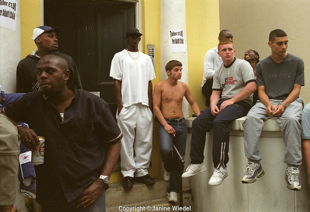 Multiracial group of young men hanging around on the  steps chatting.