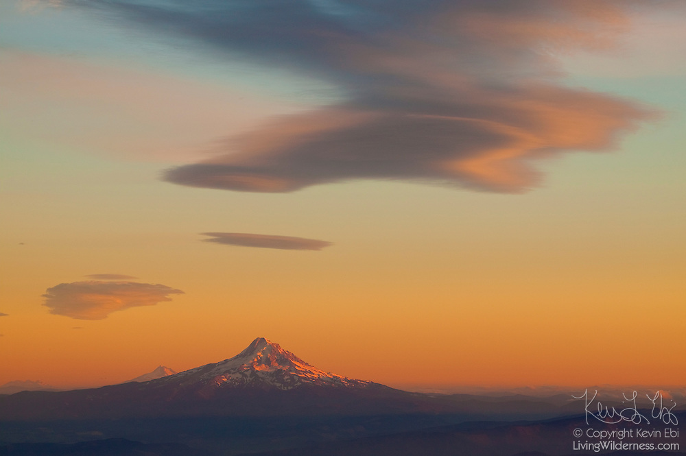 A large lenticular cloud hovers over Mount Hood, Oregon, at sunset in this view from Washington's Mount Adams. Also visible on the horizon are Mount Jefferson and the Sisters, which are located in Oregon. All these mountains are part of the Cascade range.