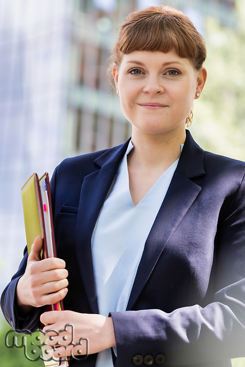 Portrait of young beautiful businesswoman standing while holding documents