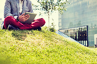 Portrait of young attractive businessman using digital tablet while sitting on the grass