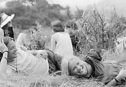 Young white male and young white female lying together laughing in field. Glastonbury 1992