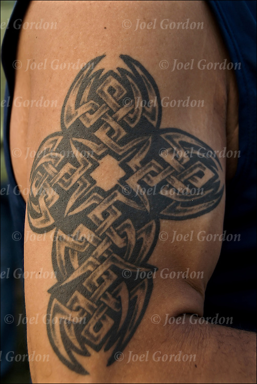 Celtic Cross Tattoo on right shoulder.<br /> <br /> Tattoos once were considered to be form of anti-conformist but not anymore.  <br /> <br /> In some cultures this is viewed as body art.  In the United States this can be seen in national advertisements and on television and the movies. Body art or tattoos has entered the mainstream it is know longer considered a weird kind of subculture.