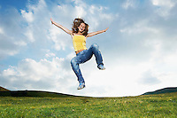 Woman jumping for joy in mountain meadow front view