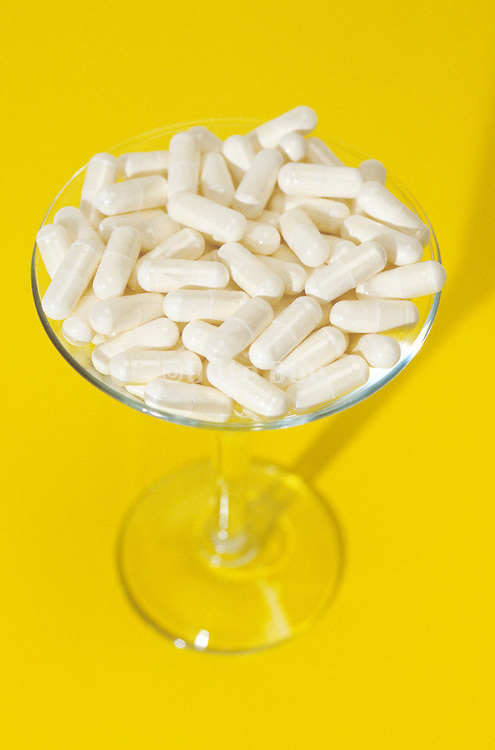 Martini glass full of pills on a yellow background