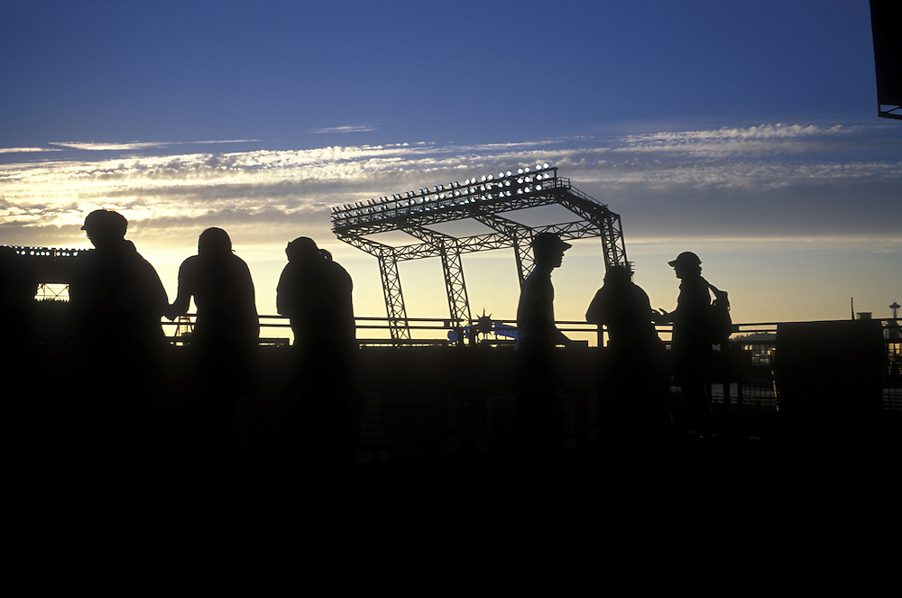USA, Washington, Seattle Mariners fans silhouetted by sunset watch baseball game from upper decks at Safeco Field