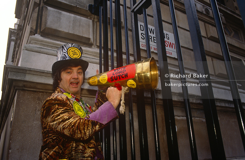 Screaming Lord Sutch holds up a megaphone to the gates of Downing Street in the run-up to the 1992 elections, on 11th March, in London UK. David Edward Sutch (10 November 1940 – 16 June 1999), also known as 3rd Earl of Harrow, or simply Screaming Lord Sutch, was an English musician. He was the founder of the Official Monster Raving Loony Party and served as its leader from 1983 to 1999, during which time he stood in numerous parliamentary elections. He holds the record for losing more than 40 elections in which he stood. Suffering from depression he committed suicide 1999.