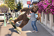 A worker moves a giant stuffed Bigfoot or Sasquatch at a shop along 4th Avenue in downtown Anchorage, Alaska.