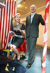© Licensed to London News Pictures. 29/09/2014. Birmingham, UK. William Hague laughs as his wife Ffion hooks a toy duck at a trade stall.  The Conservative Party Conference in Birmingham 29th September 2014. Photo credit : Stephen Simpson/LNP