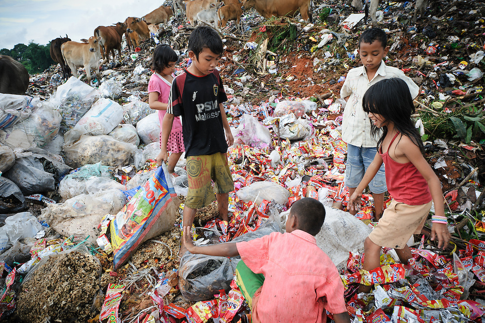 Ashuar, 12, with Erni, Sida and two unidentifed boys searching for biscuits amongst discarded waste at the 'Trash mountain', Makassar, Sulawesi, Indonesia.