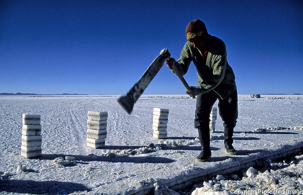Works of extracion of blocks of salt realized by Inocencio Flores.  Salar de Uyuni ( Uyuni salt flat ) . Department  of Potos&iacute;  ( Los Lipez).  South West  Bolivia. <br /> Adult Altiplano America Andes Arid  Aridity Axe Barren  Bicycle Block  Bolivia Cleaver Color Colour Cone  Day Daytime  Department  Desert Desolate Desolation Dry  Exterior Extraction  Geography Hack Hard Hatchet  Heat Highlands  Horizon Horizontal Human  Latin America Lake  Los Lipez Male Man Men Miner Mining Nature  Resource  Natural  One Outdoors Outside  Pan People  Person Pyramide Potos&iacute;  Production  Region Resource Rural Salar de Uyuni  Salt Flat  Salt Pan  Salt lake  Scenic Seasoning  Single Shape South America  Southwest  Sud Sunglasses  Surface Travel  West White Work  Worker Working