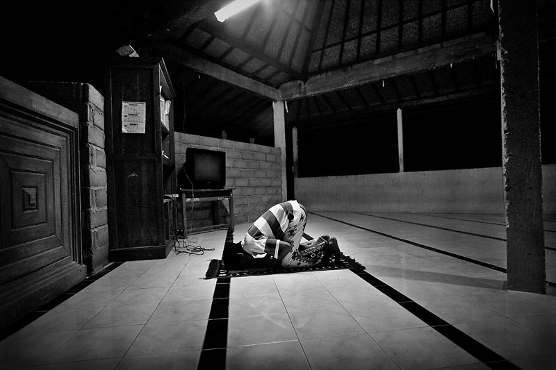Arifin, age 15, bows his head during morning prayer...Gianyar Orphanage in the Island of Bali is located not far away from many popular tourist destinations of white sand beaches, shops, clubs, and bars.  In contrast, approximately 200 children ranging from ages 8-18 lives at this overcrowded and underfunded orphanage. Each small room has about 13-17 children.  Until recently the children slept on the floor but now four kids sleep on one mattress and they have a few pillows and blankets that they too share as well.  And whatever clothes and possessions they have are kept in a locker size closet.  Most of the rooms are in need of repair.  The paint in all the rooms is peeling.  The air in many of the rooms is damp due to poor ventilation.  It's difficult to breathe inside.  Many of the windows are broken and nailed shut and the ceilings are leaking. They get three meals a day mainly consisted of rice, vegetables, tofu and soybean.  There is no doctor on-site and he only comes once a week so if a child is sick he or she must wait until the next visit. The children almost never go out of the orphanage.  There are no field trips or activities other than going to school and their daily prayers. Despite their living condition, they tried to make their rooms cozy, comfortable, and beautiful. Many had photos of their families and friends in small frames. The boys covered their wall with cartoon drawings and writings of anger, frustration, love, friendships, and broken hearts. The girls' rooms were decorated with pink and purple flowers, and posters of female artists and male heartthrobs. Though each child is clinging to any fleeting remnants of their childhood, they still they have each other to share their love, joy, laughter, dream and sadness and that's enough to keep hope afloat.