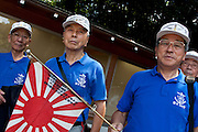 Military veterans with a small Japanese battle flag at Yasukuni Shrine. On August 15th every year people gather at Yasukuni Shrine to commemorate the end of the Pacific War. Notionally a call for remembrance and continued peace it is also a Mecca for right wing nationalist including  the paramilitary Uyoku Dantai. Tokyo, Japan, August 15th 2009