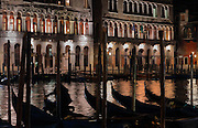 Gondolas on the Grand Canal at night, Venice, Italy. Many of the houses and palazzos fronting the canals are in Venetian Gothic style, a style originating in the 14th century and combining Gothic lancet arches with Byzantine and Moorish influences. The city of Venice is an archipelago of 117 small islands separated by canals and linked by bridges, in the Venetian Lagoon. The historical centre of Venice is listed as a UNESCO World Heritage Site. Picture by Manuel Cohen