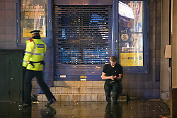 "© Licensed to London News Pictures . 23/12/2017. Manchester, UK. A police officer checks on a man's welfare on High Street . Revellers out in Manchester City Centre overnight during "" Mad Friday "" , named for being one of the busiest nights of the year for the emergency services in the UK . Photo credit: Joel Goodman/LNP"