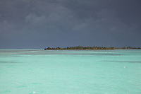 Black skies from a huge thunderstorm over the clear turquoise waters of the Caribbean near Belize.