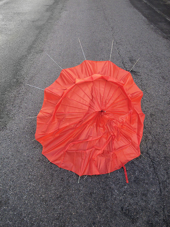 A bright orange umbrella damaged by a wind and rain storm rests on the pavement.  The ribs of the umbrella stick out from the fabric that has been torn away.