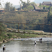 Black Hmong men fishing at Lao chai village near Sapa, Northern Vietnam.  Sapa and the surrounding highlands are close to the Chinese border in Northern Vietnam and is inhabited by highland minorities including Hmong and Dzao groups. Sapa is now a thriving tourist destination for travelers taking the night train from Hanoi. Sapa, Vietnam. 16th March 2012. Photo Tim Clayton