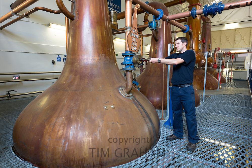 Stillsman inspecting copper spirit stills in the Stillshouse at Talisker Whisky Distillery making single malt whisky in Carbost on Isle of Skye, Scotland