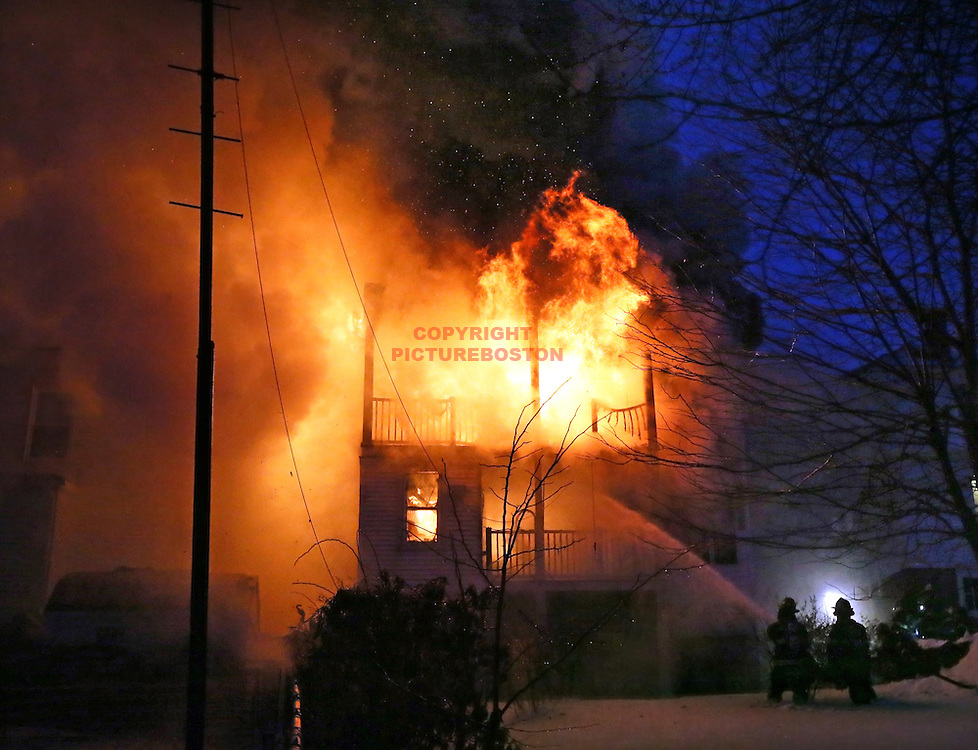 02/06/2015-Revere, MA. Firefighters battle flames, smoke and cold air at the scene of a 3 alarm fire on Reservoir Ave. Friday morning. Staff photo by Mark Garfinkel