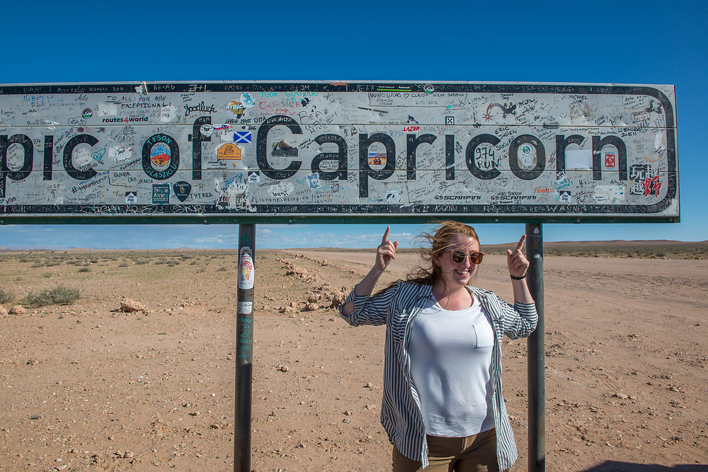 Tourists pose in front of the Tropic of Capricorn sign in the Namib desert, located in Namibia, Africa. The Tropic of Capricorn is part of a world map that indicates the division between the southern temperate zone and northern tropics.