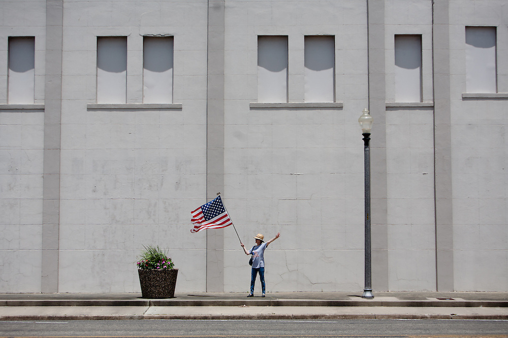 Chris Hicks, a member of the Wharton Tea Party, waves an American flag in downtown El Campo, Texas in support of wounded veterans passing through town on their way to the Gulf Coast.