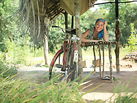 Portrait of young woman lying in hut smiling bicycle leaning on pale