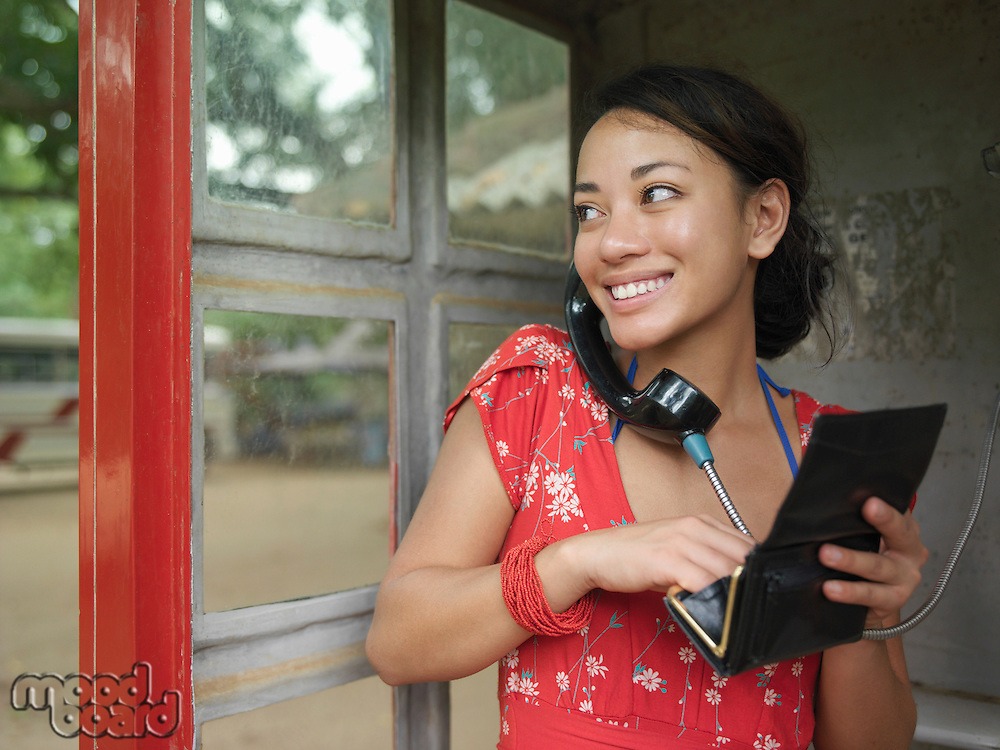 Young woman using public phone looking over shoulder holding purse smiling