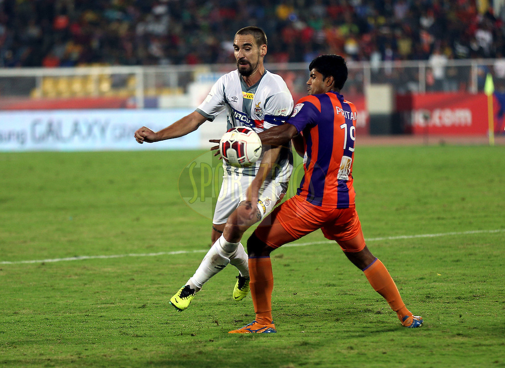 Fikru Tefera Lemessa of Atletico de Kolkata and Pritam Kotal of FC Pune City during match 44 of the Hero Indian Super League between FC Pune City and Atletico de Kolkata FC held at the Shree Shiv Chhatrapati Sports Complex Stadium, Pune, India on the 29th November 2014.<br /> <br /> Photo by:  Sandeep Shetty/ ISL/ SPORTZPICS